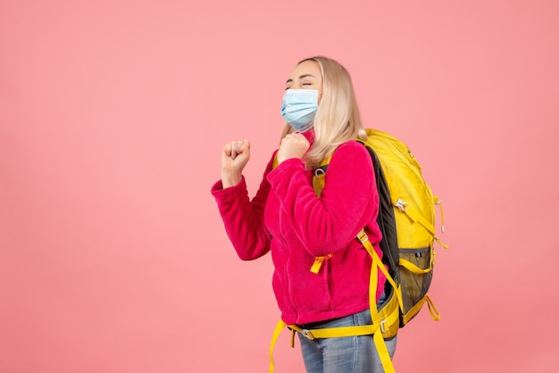 目を閉じてマスクを身に着けている黄色のバックパックと正面の旅行者の女性