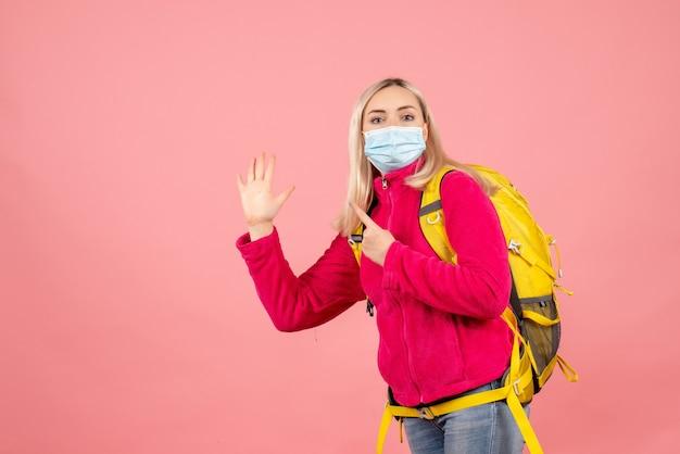 ハイタッチを与えるマスクを身に着けている黄色のバックパックを持つ正面図の旅行者の女性