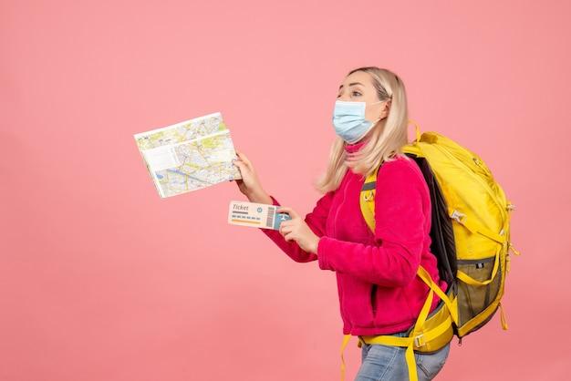 Женщина-путешественница с желтым рюкзаком в маске, держащая карту и билет, вид спереди