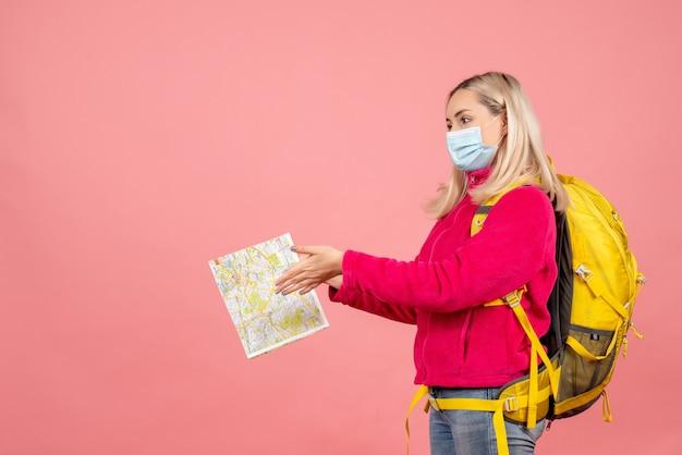 Женщина-путешественница с желтым рюкзаком в маске, держащая карту, вид спереди