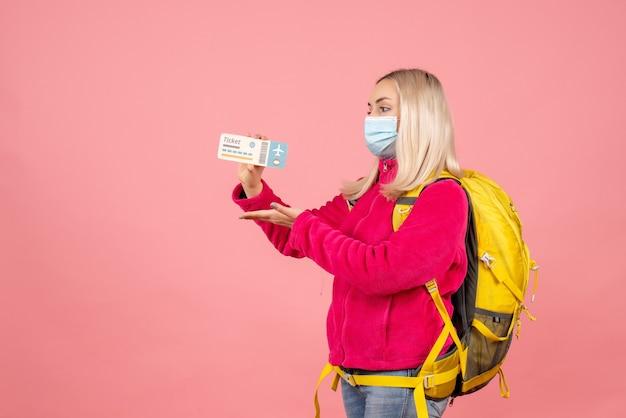 Женщина-путешественница с желтым рюкзаком в маске, держащая билет, вид спереди