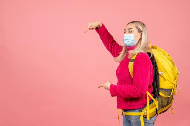 Donna del viaggiatore di vista frontale con lo zaino giallo che indossa la maschera che indica qualcosa