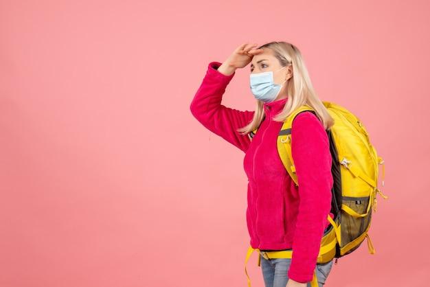 그녀의 이마에 손을 넣어 마스크를 쓰고 노란색 배낭과 전면보기 여행자 여자