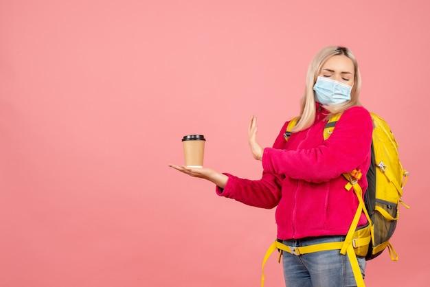 コーヒーを拒否するマスクを身に着けている黄色のバックパックと正面の旅行者の女性