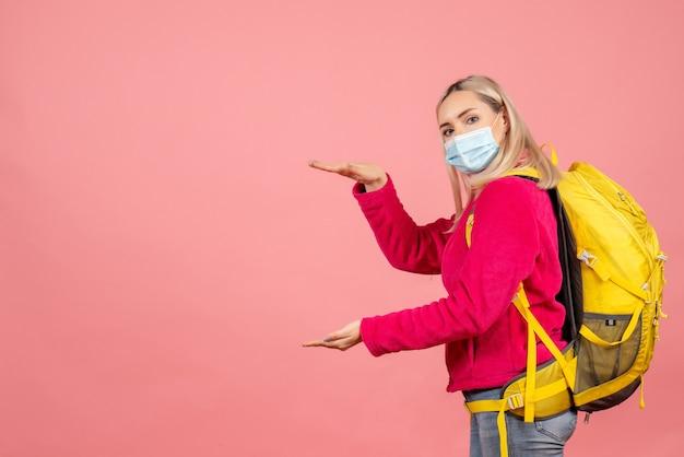 手でサイズを示すマスクを身に着けている黄色のバックパックと正面の旅行者の女性