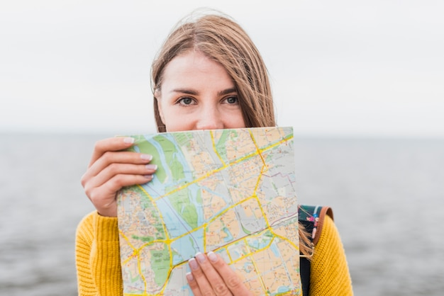 Front view of traveling woman holding map