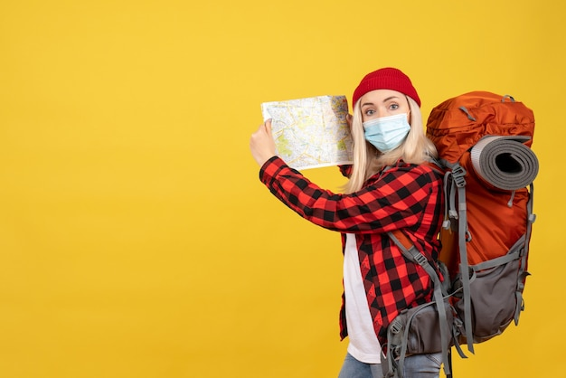 Девушка-путешественница, вид спереди с рюкзаком, подняв карту