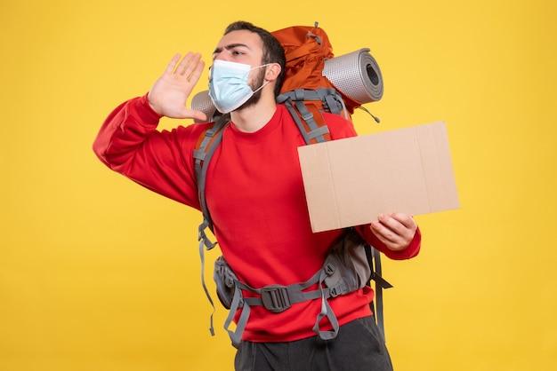Vista frontale del viaggiatore che indossa una maschera medica con zaino che mostra un foglio senza scrivere chiamando qualcuno su sfondo giallo yellow
