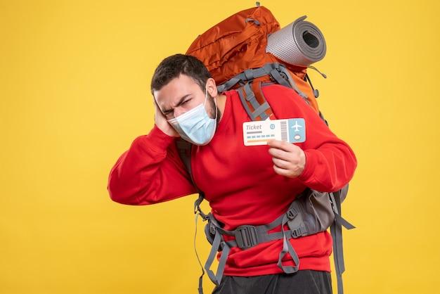 Vista frontale del viaggiatore che indossa una maschera medica con uno zaino che mostra il biglietto e si sente nervoso su sfondo giallo
