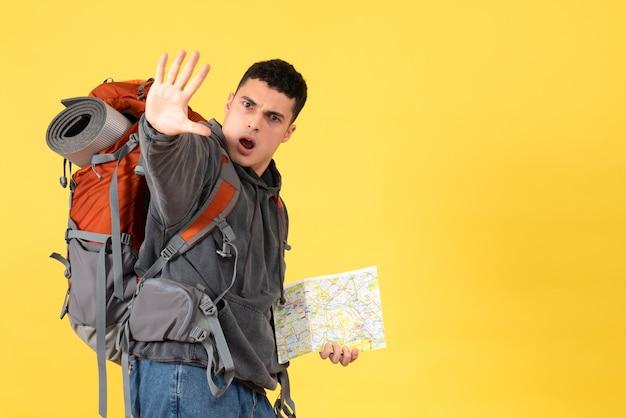 Человек путешественника вид спереди с рюкзаком, держащим карту, делая знак остановки