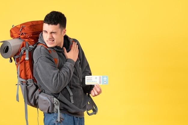 痛みで彼の心を保持しているチケットを保持しているバックパックを持つ正面図の旅行者の男性