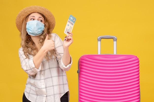 Vista frontale della ragazza in viaggio che indossa la maschera che mostra il biglietto e in piedi vicino alla sua borsa rosa che fa il gesto giusto su giallo