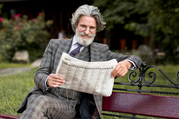 Front view trendy mature man reading newspaper