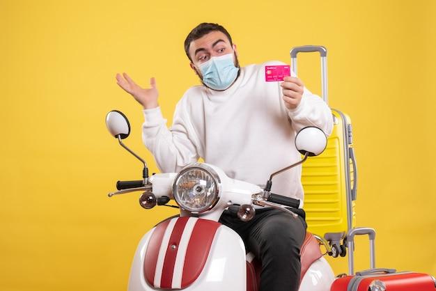 Vista frontale del concetto di viaggio con giovane ragazzo interessato in maschera medica seduto in moto con valigia gialla su di esso e in possesso di carta di credito