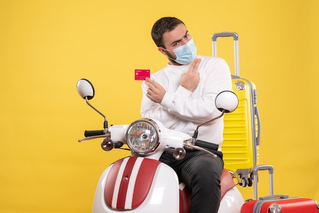 Vista frontale del concetto di viaggio con un giovane ragazzo fiducioso in maschera medica seduto su una moto con valigia gialla su di esso e in possesso di carta di credito