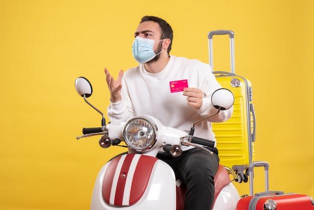 Vista frontale del concetto di viaggio con un giovane ragazzo curioso in maschera medica seduto su una moto con valigia gialla su di esso e in possesso di carta di credito