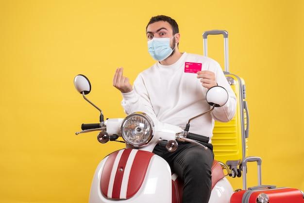 Vista frontale del concetto di viaggio con giovane ragazzo sorpreso in maschera medica seduto su una moto con valigia gialla su di esso e in possesso di carta di credito