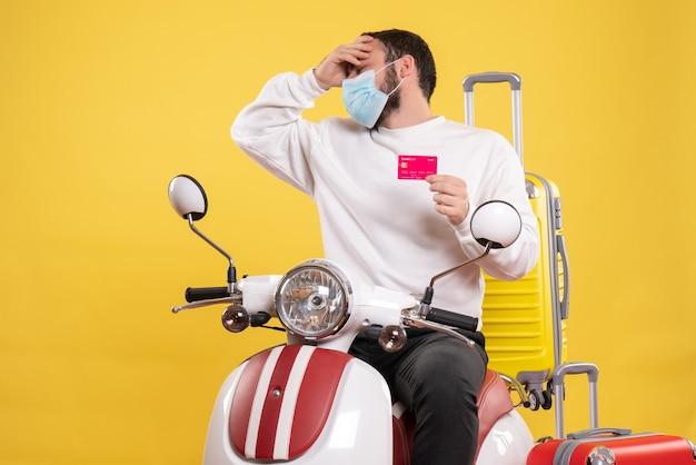 Vista frontale del concetto di viaggio con un ragazzo problematico in maschera medica seduto su una moto con valigia gialla su di esso e in possesso di carta di credito