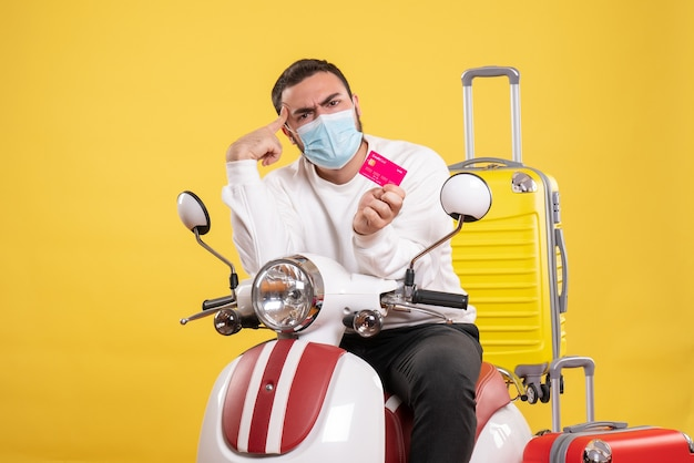 Vista frontale del concetto di viaggio con giovane ragazzo confuso in maschera medica seduto su una moto con valigia gialla su di esso e in possesso di carta di credito