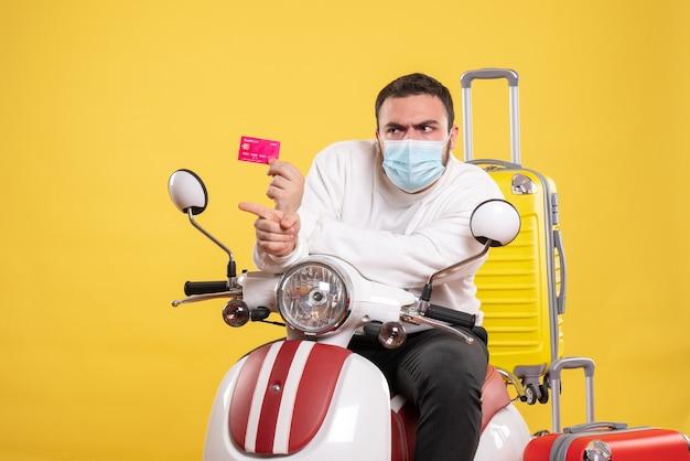 Vista frontale del concetto di viaggio con un giovane ragazzo curioso in maschera medica seduto su una moto con valigia gialla su di esso e con in mano una carta di credito che indica qualcosa