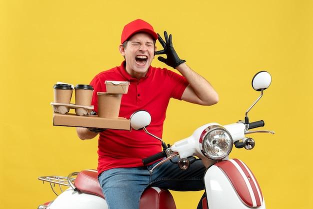 Vista frontale del travagliato corriere uomo che indossa camicia rossa e guanti cappello in maschera medica consegna ordine seduto su scooter tenendo gli ordini chiudendo il suo orecchio