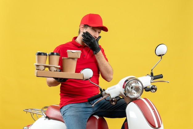 Front view of troubled courier man wearing red blouse and hat gloves in medical mask delivering order sitting on scooter holding orders suffering from toothache