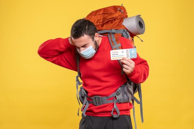 Vista frontale di un viaggiatore problematico che indossa una maschera medica con uno zaino e mostra un biglietto che soffre di mal di testa su sfondo giallo