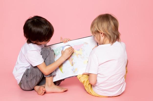 Вид спереди два мальчика рисуют в белых футболках на розовом столе