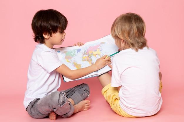 Vista frontale due ragazzi che disegnano mappe in magliette bianche sul pavimento rosa