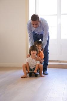 Vista frontale di due ragazzi che guidano sullo skateboard a casa. padre attraente caucasico che spinge i suoi adorabili figli indietro e gioca con i bambini. infanzia, attività di gioco e concetto di fine settimana