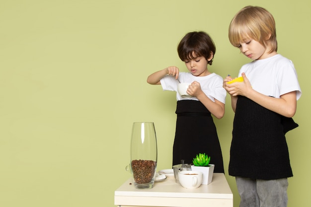 A front view two boys in white t-shirts eating on the stone colored desk