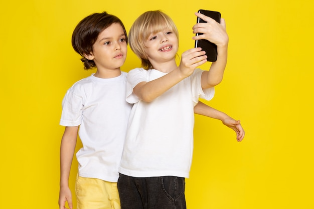 Front view two boys in white t-shirts taking selfie on yellow desk