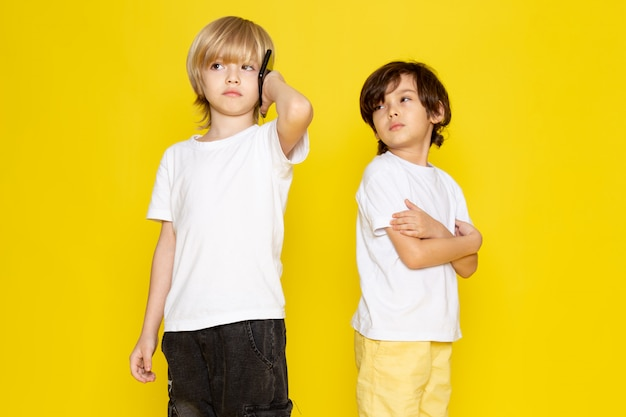 Front view two boys in white t-shirts on yellow
