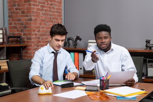 사무실에서 일하는 두 비즈니스 파트너 중 한 명이 손가락 카메라를 가리키는 전면 보기