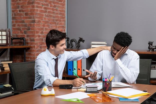 전면 보기 프로젝트에 대해 논의하는 두 사업가 중 한 명이 다른 사람의 어깨에 손을 얹고 있습니다.