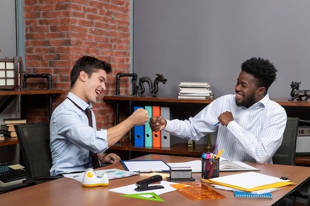 正面図2人のビジネスマンの拳が一緒にぶつかる