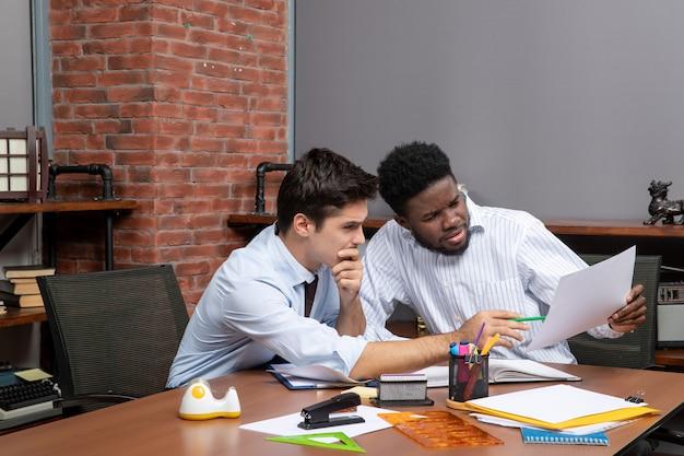 사무실에서 함께 일하는 만족스러운 두 사업가의 전면 모습