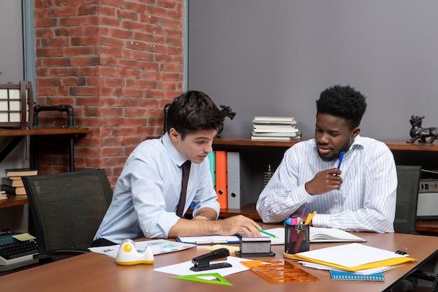 正面図机に座ってオフィスで書類をチェックする2人のビジネスマン