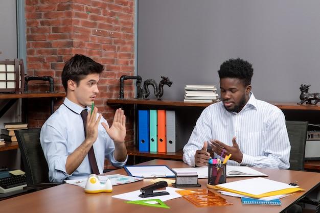 机に座って、オフィスで問題を議論している2人のビジネスマンの正面図