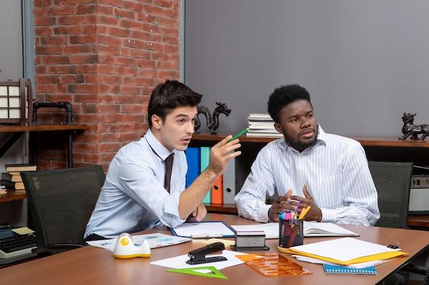 책상에 앉아 사무실에서 무언가를 보고 있는 두 사업가의 전면 모습