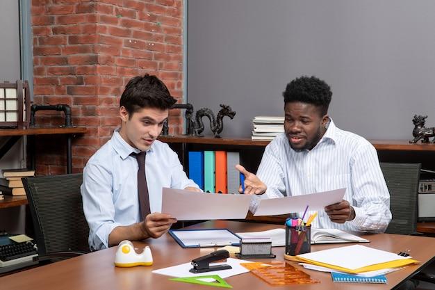 正面図テーブルの上で一緒にオフィスのものを働いているフォーマルな服装で忙しい2人のビジネスマン