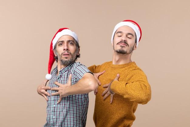 Vista frontale due uomini fiduciosi con cappelli di babbo natale che mettono le mani al petto su sfondo isolato
