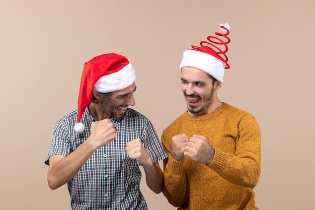 Vista frontale due uomini fiduciosi con cappelli di babbo natale che mostrano il gesto vincente su sfondo isolato