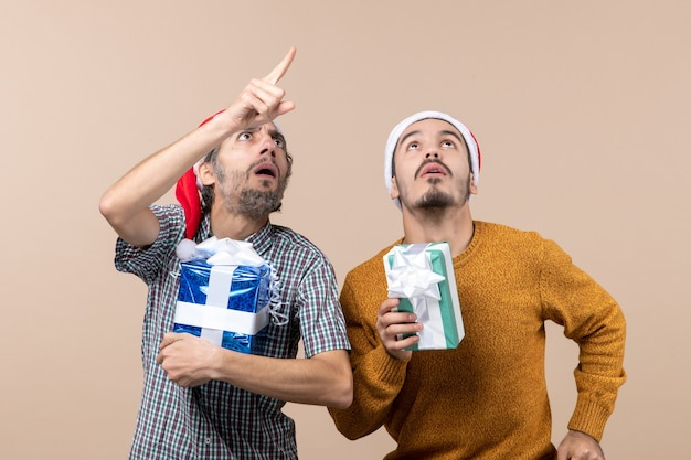 Vista frontale due ragazzi confusi che tengono i regali di natale e guardando in alto su sfondo beige isolato