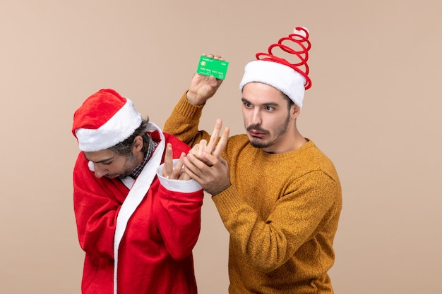 Front view two confused guys one with santa coat looking at floor and the other holding card on beige isolated background