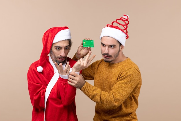 Front view two confused guys one with santa coat and the other holding card on beige isolated background