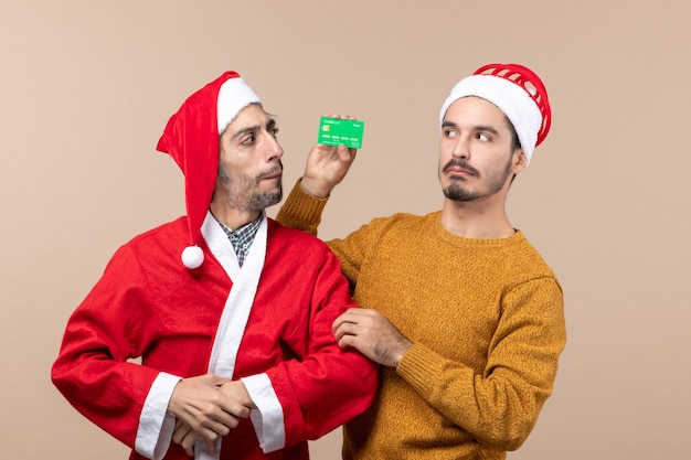 Front view two confused guys one with santa coat and the other holding card looking at each other on beige isolated background