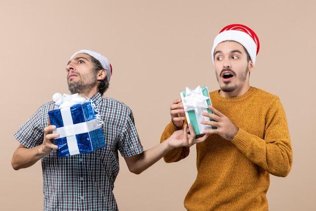 Vista frontale due ragazzi confusi, cercando di cambiare i loro regali di natale su sfondo beige isolato