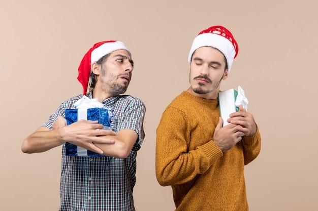 Vista frontale due ragazzi confusi che indossano cappelli di babbo natale e tengono stretti i loro regali su sfondo beige isolato