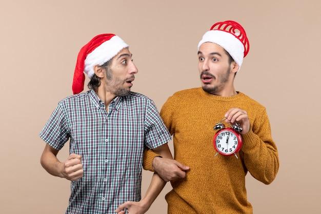Vista frontale due uomini confusi uno che tiene il braccio degli altri mentre si trovava su sfondo beige isolato